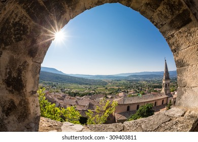 Church in Saint-Saturnin-les-Apt, seen through ruined fortress window above. City is situated at dominant position on Monts de Vaucluse facing south towards Luberon. It has around 3000 inhabitants.