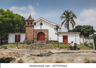 Church of San Antonio above the city of Cali, Colombia, on a sunny day with some clouds. Motorcyclist is just driving past the church