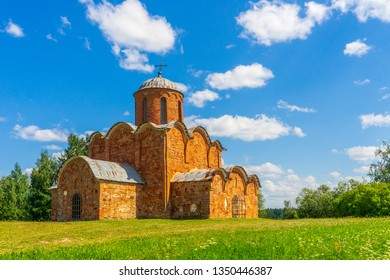 Church of the Savior on Kovalev, Velikiy Novgorod vicinity, Russia. Russian landscape with green trees, grass and ancient orthodox temple against blue sky. Beautiful scenery and architectural landmark