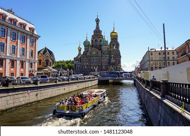 The Church of the Savior on Spilled Blood in Saint Petersburg with a tourist boat passing by in a canal. Saint Petersburg, Russia. June 29, 2019.