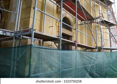 Church scaffolding. Restoring old monastery. Scaffolding construction.  Repair of the facade on a historic building. Baroque monastery in the village Dolni Rocov, Czech Republic.