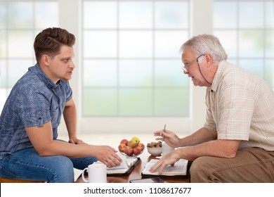 Church servant doing spiritual counseling to a young man studying the Bible