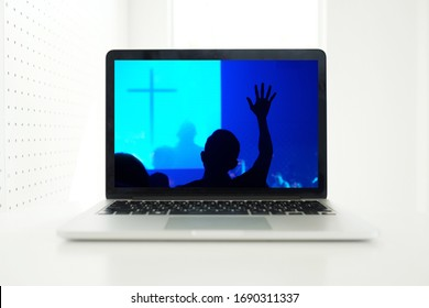 Church services online concept, Home church during quarantine coronavirus Covid-19, Online church from home new normal concept, Cross with worship hand in screen laptop, spirituality and religion. - Shutterstock ID 1690311337