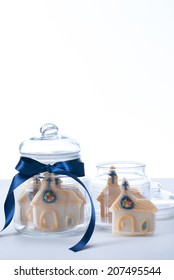 Church shaped cookies in two clear cookie jars with blue ribbon. Sot with copy space.