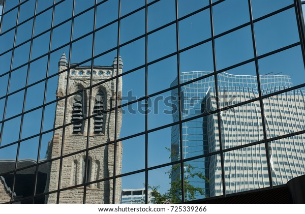 Church and skyscrapers reflected in glass front of office building in Minneapolis