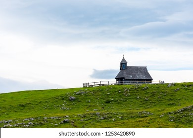 Church in the Slovenia big plateau pasture (Velika Planina). Chapel on the hill, religion symbol. Green meadow and blue sky with clouds. Plateau near the Kamnik city.