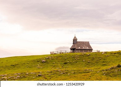 Church in the Slovenia big plateau pasture (Velika Planina). Chapel on the hill, religion symbol.Dramatic mystic clouds and colors. Green meadow and blue sky with clouds. Plateau near the Kamnik city.