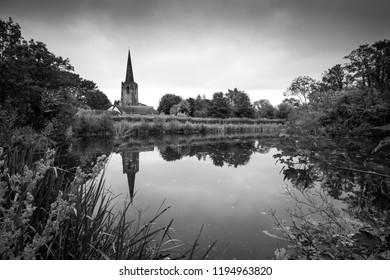 Church spire reflected in still water