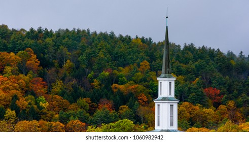 Church spire rising out of the peak fall folioage of Vermont