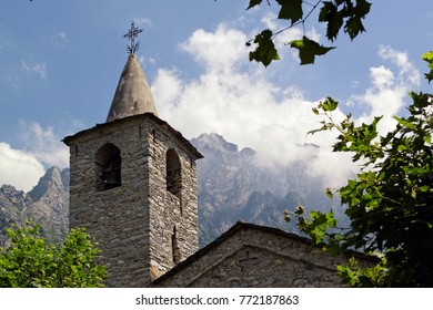 Church spire and roof of an old church in a mountain village in the alps