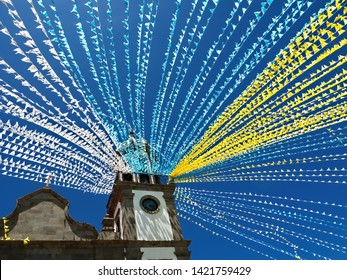 a church square decorated with colorful garlands for a traditional festival in Tenerife. The blue-white-yellow flags blow in the wind under a dark blue sky