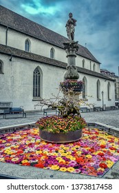 A church square fountain decorated with flowers in central Zurich