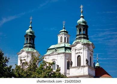 The Church of St. Nicholas behind the trees in Prague, Czech Republic