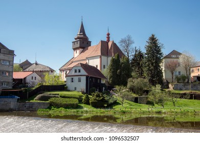 Church of St. Wenceslas in town Svetla nad Sazavou, clock tower, sunlight, greenery and blue sky, river Sazava and water reflections - Shutterstock ID 1096532507