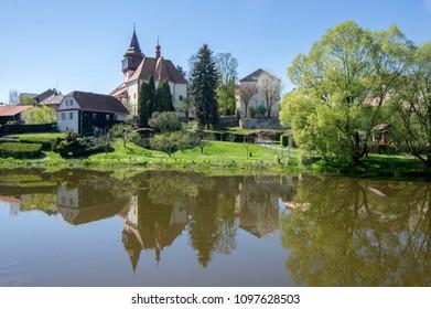 Church of St. Wenceslas in town Svetla nad Sazavou, clock tower, sunlight, greenery and blue sky, river Sazava and water reflections - Shutterstock ID 1097628503