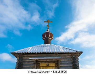 Church steeple above a small chapel on the background of blue sky with white clouds.
