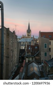 Church steeple against a colorful evening sky in France