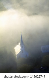 Church steeple wreathed in morning fog in autumn, Waitsfield, VT