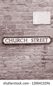 Church Street Road Sign on Stone Wall in Black and White Sepia Tone