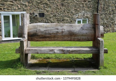 Church Streeton, Shropshire, England, UK.  April 9, 2019.  A rough hewn wooden bench, with inscription, in a quiet corner of the churchyard.