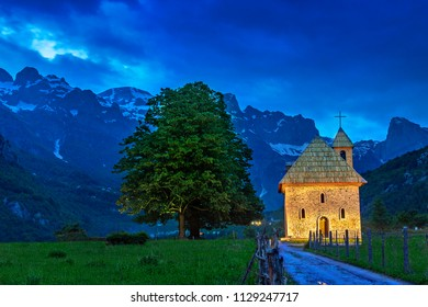 Church in the Thethi Village and snow capped mountains, at the twilight, in the Theth Valley, Albania.