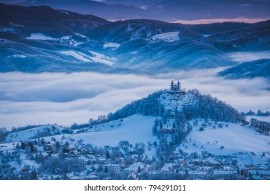 Church at the top of the hill in calm blue  winter morning. Banska Stiavnica, Slovakia