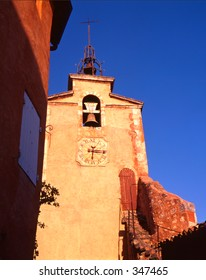 Church tower with bell and clock in Provence, south of France