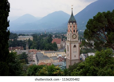 Church tower and city view of the meran, italy. Mountains in the distance. Clouds day. Trees in front. scenic view. Travel background. South tirol. Alto adige.