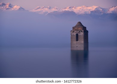 Church tower coming out of the water on a foggy day with mountains in the background