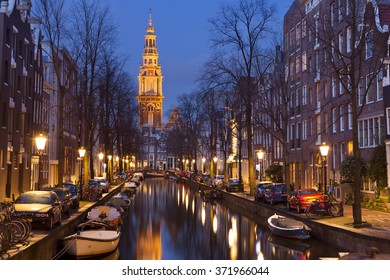 A church tower at the end of a canal in the city of Amsterdam, The Netherlands at night.