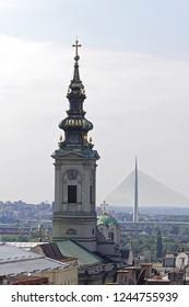 Church tower and new Ada bridge pylon in Belgrade Serbia