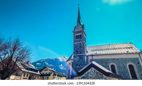 Church tower on blue sky background and rainbow in Alps, Niedernsill, Austria