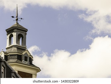 church tower with weathervane and blue sky with clouds in Spain