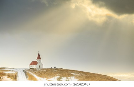 The church at Vik, Iceland with sunbeams coming out of snow storm clouds.