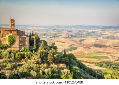 Church and village of Montalcino, countryside landscape in the background, Tuscany, Italy
