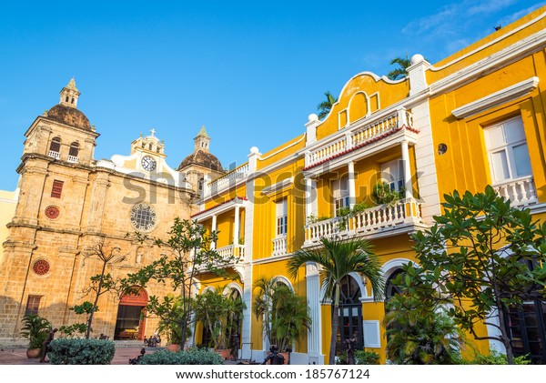 Church and yellow colonial building visible from San Pedro Claver plaza in historic Cartagena, Colombia