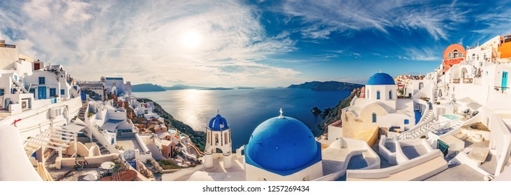 Churches in Oia, Santorini island in Greece, on a sunny day with dramatic sky. Panorama view.