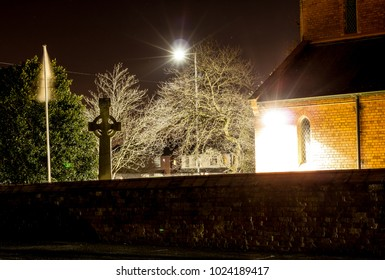 The churchyard at night time with the red bricks and cross