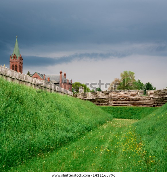 A Churge outside the wooden picket fence and battlements of Fort Stanwix.