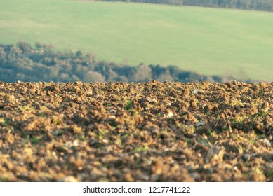Churned up mud, as a result of ploughing,  leading into the distance with rolling hills beyond