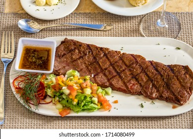 Churrasco beef meat with vegetables and sauce on a white plate, restaurant dish