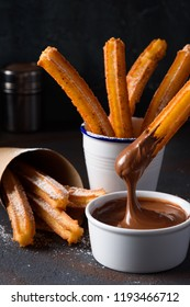 Churro with sugar powder and cinnamon in melted chocolate dip