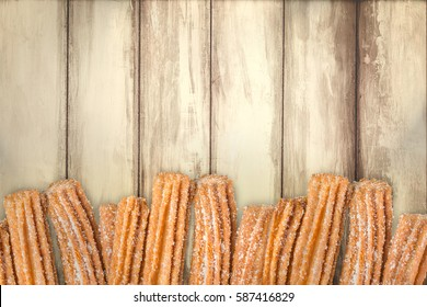 Churros arranged in row on wooden background