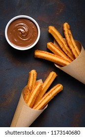Churros with cinnamon and chocolate sauce on dark background flat lay top view