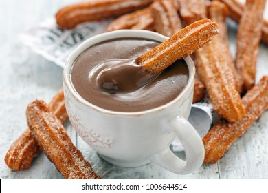 Churros with a cup of hot chocolate closeup, selective focus.
