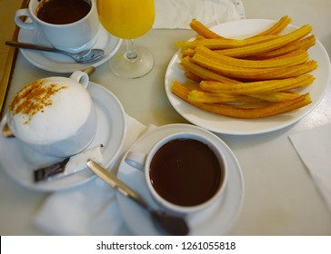 Churros, hot chocolate and cappuccino on a table in a cafe