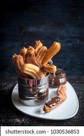 Churros with melted chocolate,selective focus
