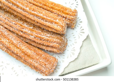 Churros on a plate decorated with napkin on white background
