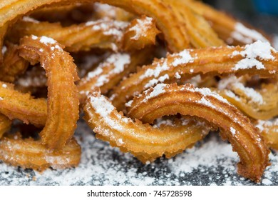 Churros on plate decorated with powdered sugar. Traditional mexican dessert closeup