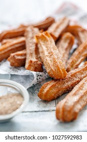 Churros sprinkled with sugar and cinnamon on white wooden table, selective focus.